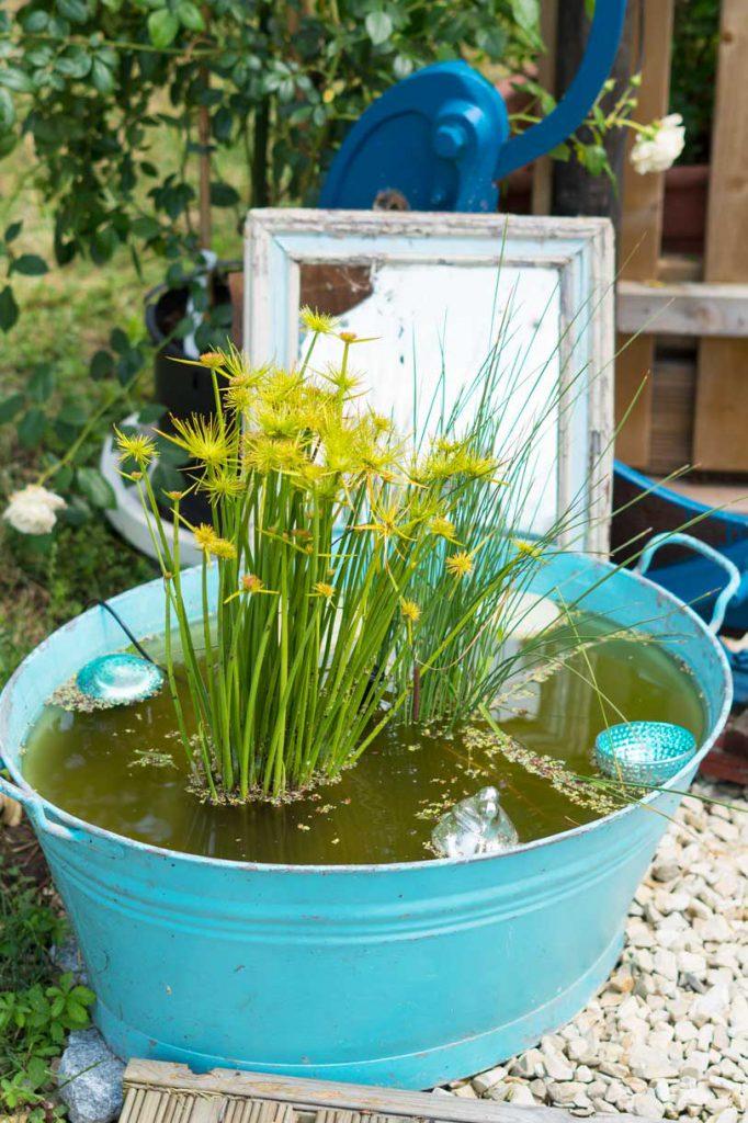 Gartendekoration mit türkisfarbener Zinkwanne, Wasserpflanzen und einem dahinter aufgestellten SpiegelSpiegel