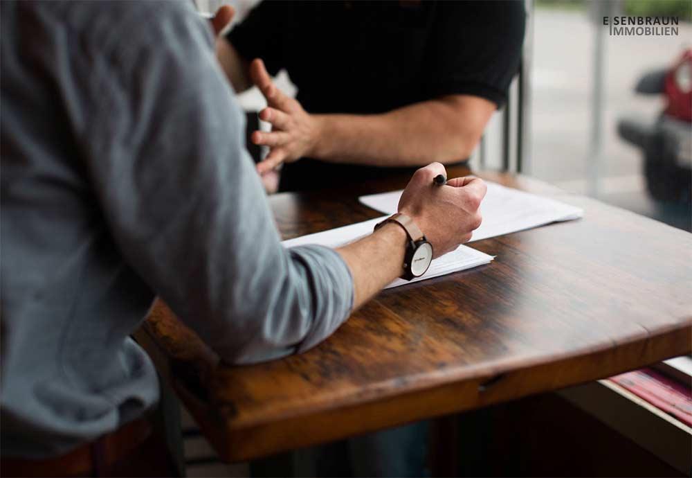 Zwei Männer Unterhalten Sich An Einem Tisch. Titelbild Für Den Magazin-Beitrag: Fünf Tipps Für Den Kauf Einer Immobilie